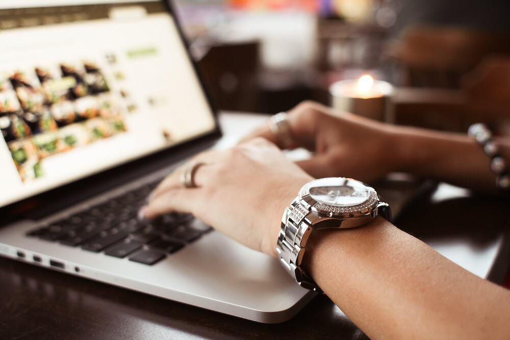 Girl with Watches typing on MacBook