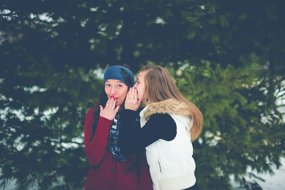 woman whispering in other woman's ear
